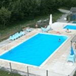 Een groot, rechthoekig zwembad met zitjes er bij.