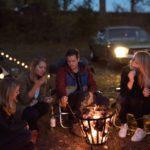 Een aantal vrienden zitten in de avond rond een vuurkorf