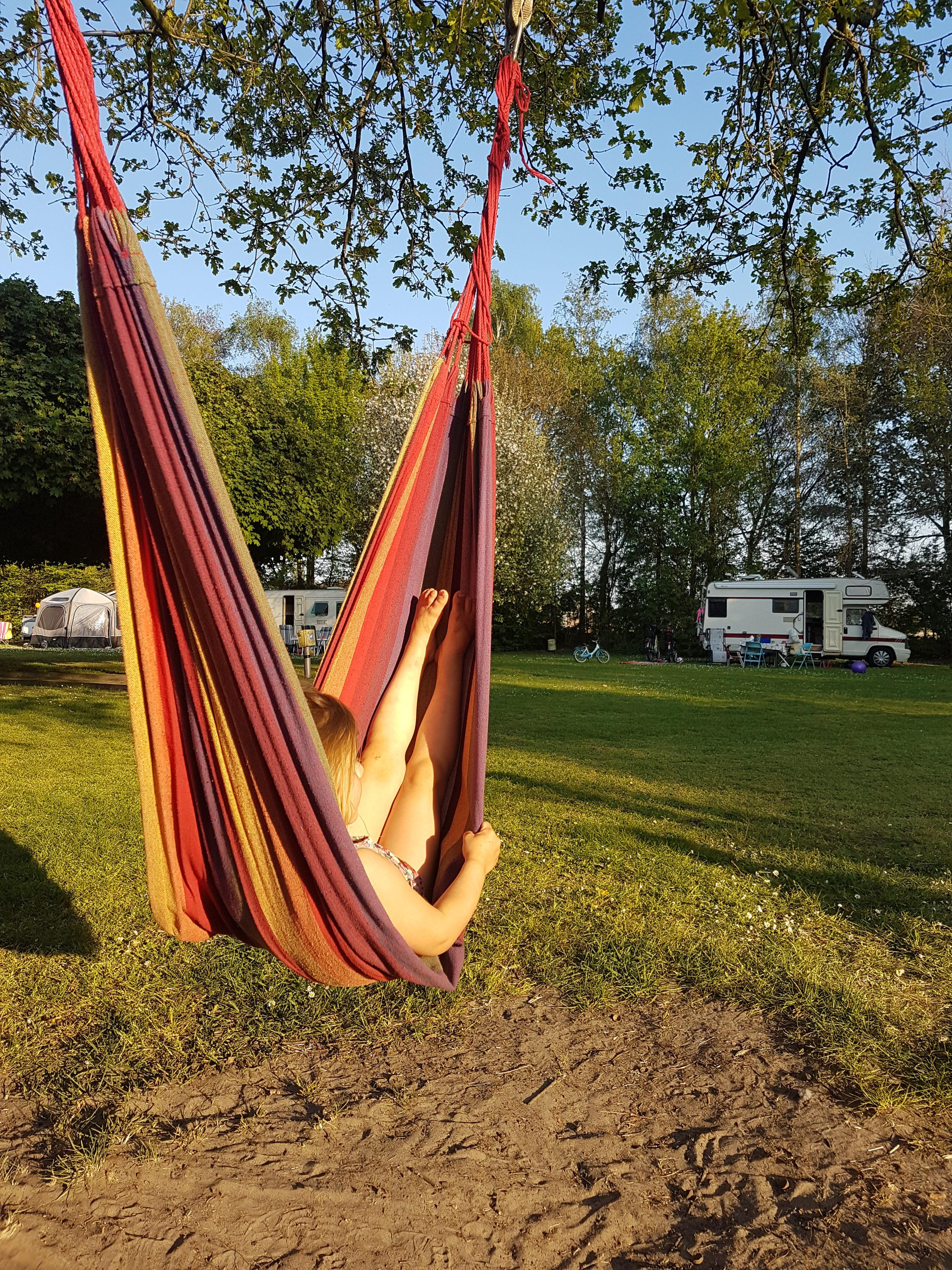 Een gekleurde hangmat in de boom met een kindje er in.