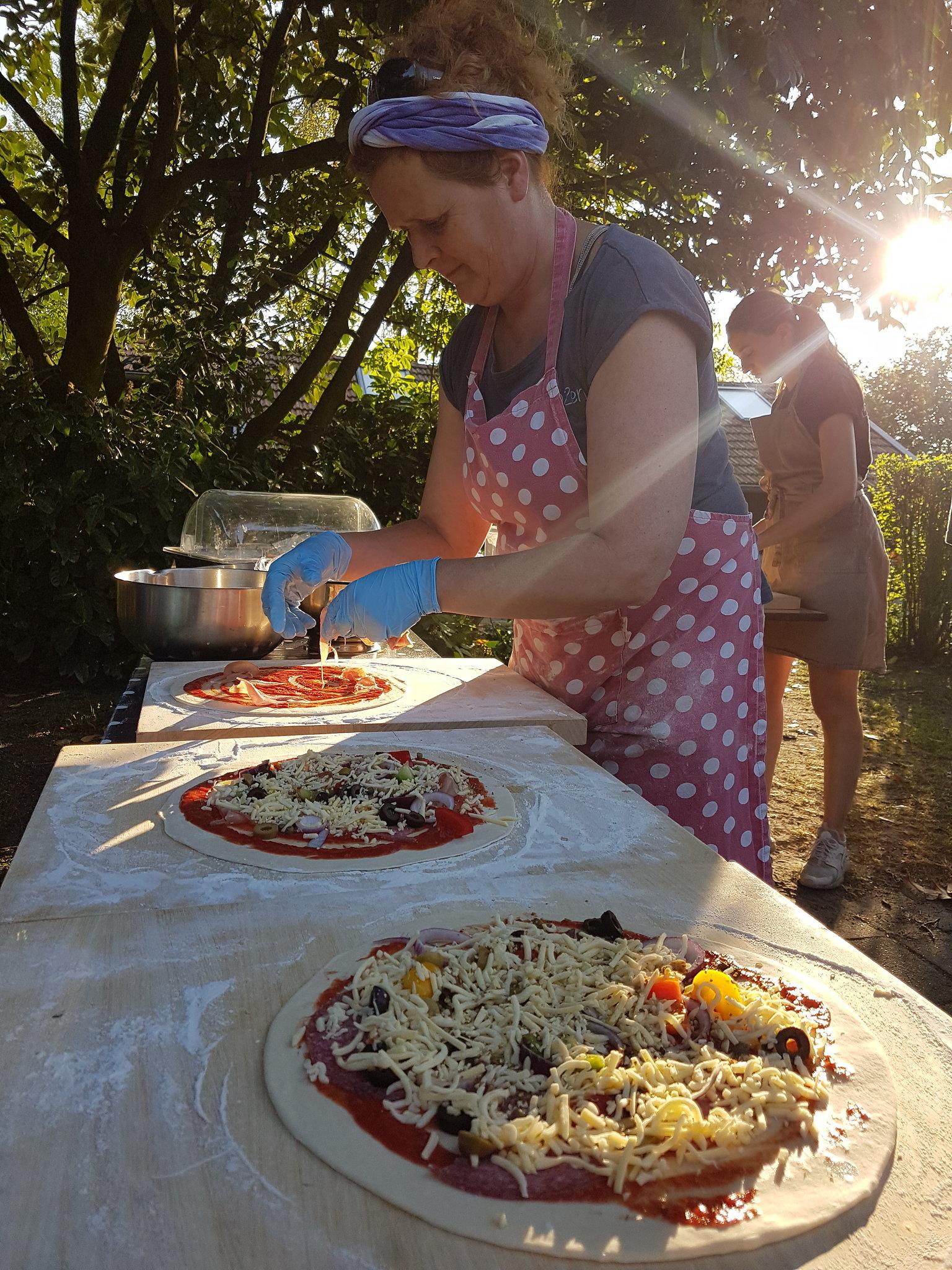 Twee vrouwen staan pizza's te maken aan een lange tafel in de buitenlucht
